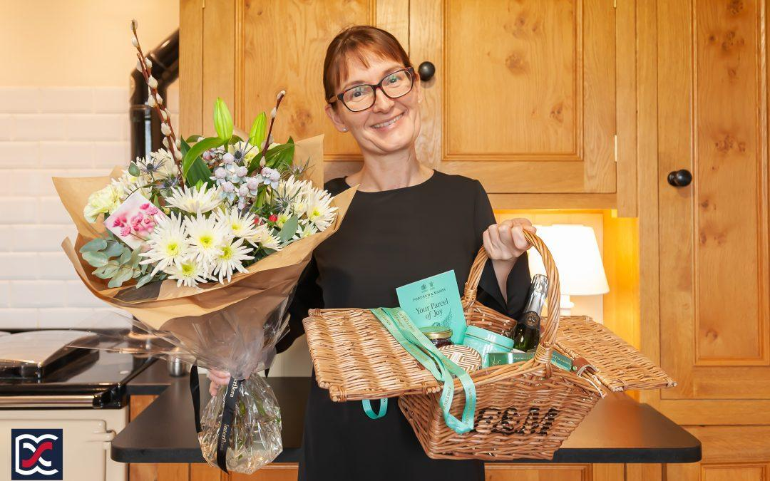 Christmas Comes Early. Natasha Cosby of David Cosby Estate Agents holding a beautiful bouquet of flowers and a delicious hamper.